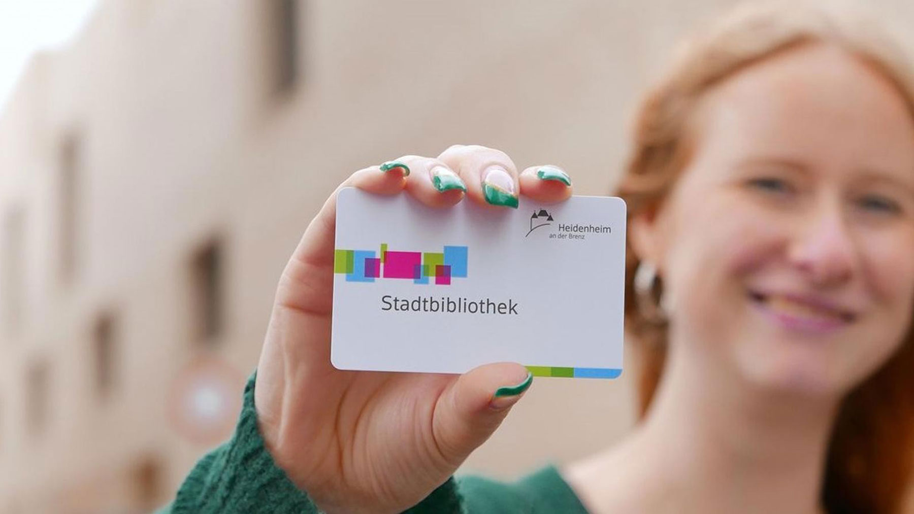 Woman holding a membership card of the library of the city Heidenheim
